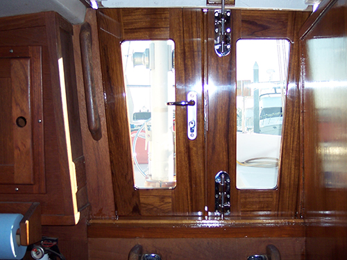 Fully secured teak companionway doors with stainless steel bars and lock.