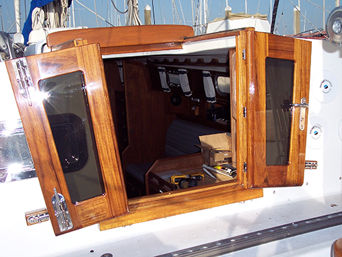 Teak companionway doors with stainless steel latches and handle.
