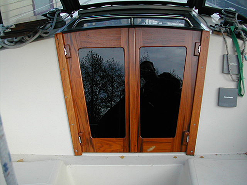 Custom built teak companionway doors with an arched top.