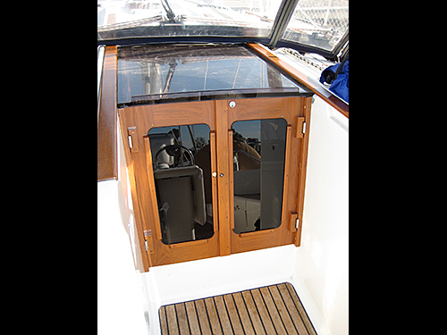 Teak companionway doors with hinge pins and lock visible.