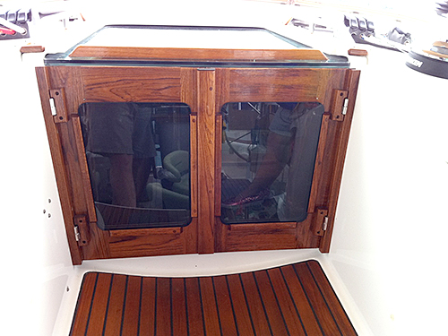 Companionway doors with a matching teak floor grate.